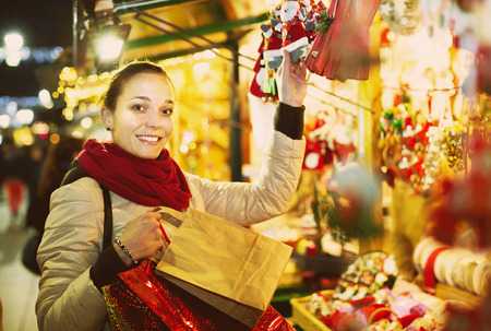 lifestile: young european girl shopping at festive fair before Xmas in evening time