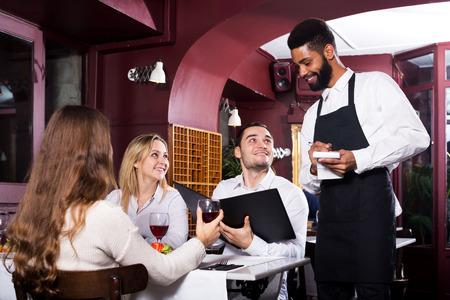 clase media: Retrato de gente alegre en el restaurante de clase media y el camarero negro Foto de archivo