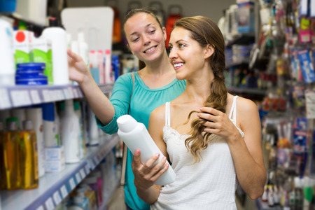 spanish girl: happy spanish girl buying shampoo in shopping mall