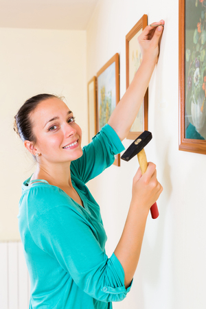 parade of homes: Ordinary positive woman with picture and hammer in her hand at house Stock Photo