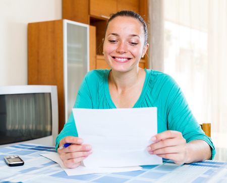 tax forms: Beautiful young woman filling out tax forms while sitting at her desk