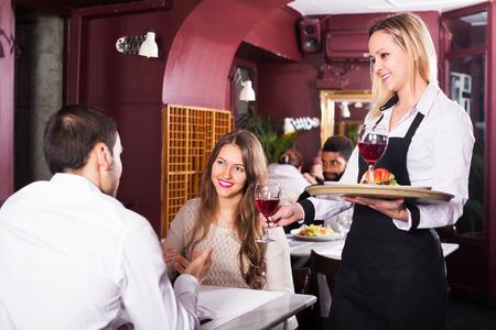 clase media: Feliz pareja joven que se fecha en el restaurante de clase media