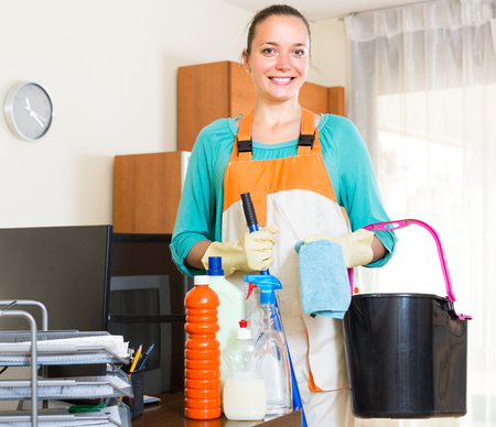household tasks: Smiling  woman in uniform with detergents and rags standing in office room
