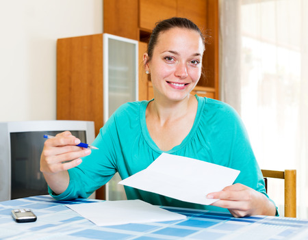 tax forms: Smiling young woman filling out tax forms while sitting at her desk