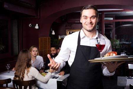 clase media: Retrato de los adultos en el restaurante de clase media y camarero joven alegre