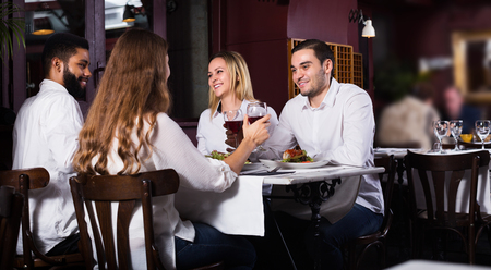 restaurant tables: Group of smiling friends having dinner in restaurant and laughing Stock Photo
