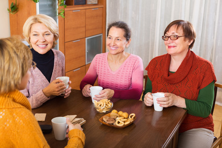 talkative: Mature pensioners having cup of hot tea indoor and smiling