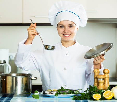 ready to cook food: Positive woman in cook uniform waiting food to be ready