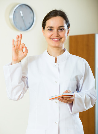 overall: Portrait of positive smiling female doctor in white overall in clinic Stock Photo