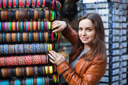 Excited  positive brunette choosing souvenir for memory and smiling Stock Photo