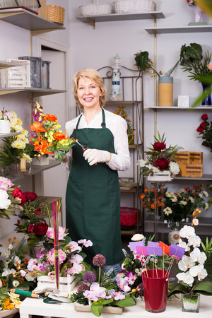 clippers: Smiling mature female florist with clippers preparing flowers for sale