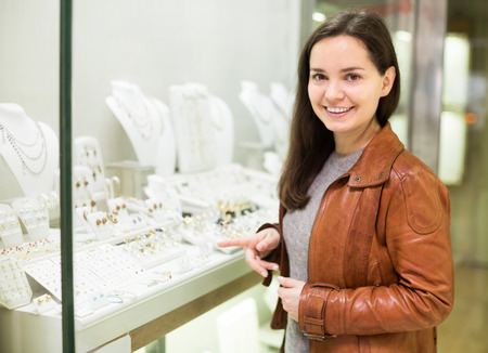 neckless: Smiling woman customer admiring jewellery in display of boutique
