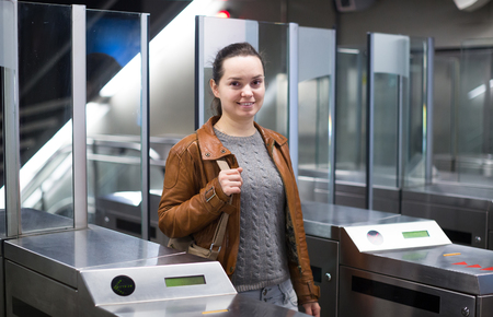baffle: Charming brunette young woman passing ticket barrier and smiling Stock Photo