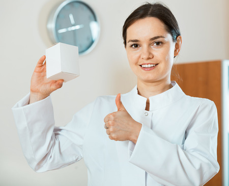 new medicine: Professional positive doctor offering new medicine and smiling in clinic Stock Photo