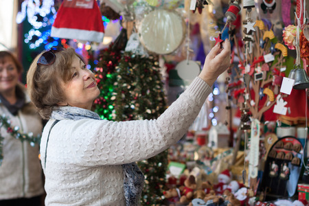 considering: Cheerful female pensioner considering X-mas decorations at fair Stock Photo
