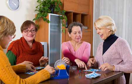 table games: Several happy female pensioners playing board game at the room in the home Stock Photo