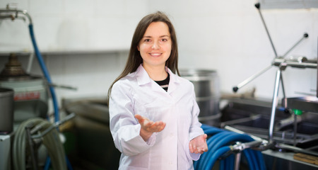 bottling: Smiling young woman near oil bottling machine in manufacturing environment