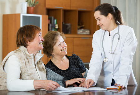 75s: Professional female doctor consulting mature women in clinic interior