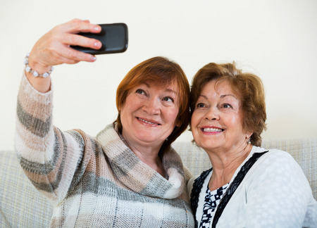 75s: Cheerful satisfied mature women using mobile phone for image together