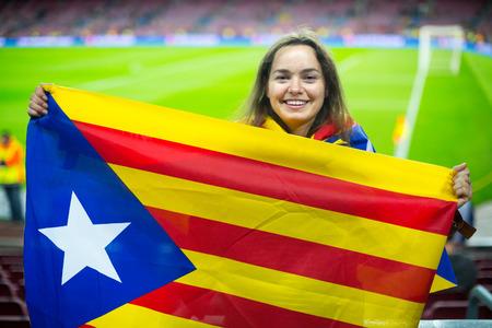 fandom: brunette female football fan with flag of Catalonia at stadium