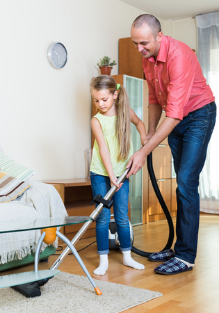 cleanup: Smiling father teaching cute little daughter vacuuming during clean-up at home
