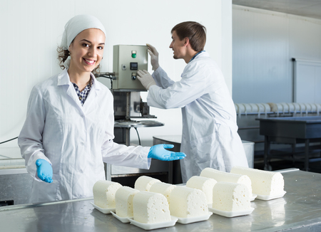 technologists: Two friendly smiling young technologists in lab coats working at dairy farm lab Stock Photo