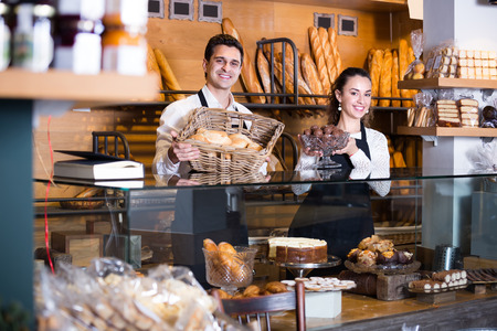 armenian woman: Positive smiling man and hospitable girl offering delicious pastry at bakery