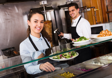 restaurant staff: Young restaurant staff posing at kebab counter and smiling Stock Photo