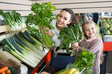 purchasers: Cheerful smiling mother with small daughter buying fresh celery and cabbage at market