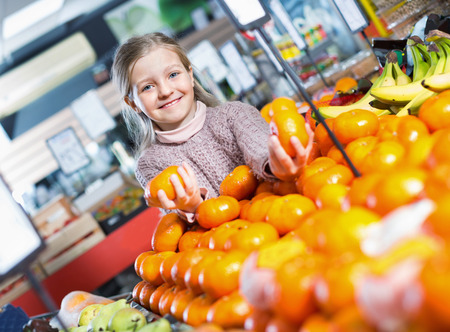 purchasers: Cheerful smiling little girl purchasing sweet mandarines in grocery Stock Photo