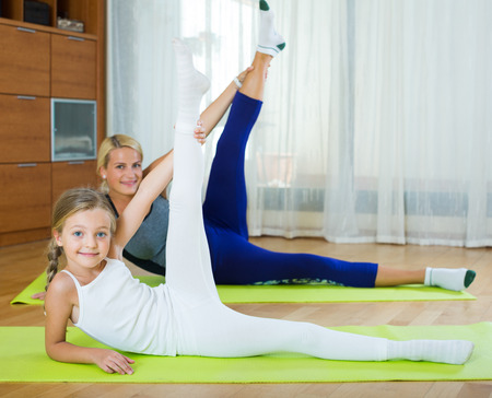 perspire: Young mother with small daughter working out and smiling