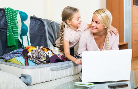 25s: Happy young blonde woman with little daughter planning vacation at home