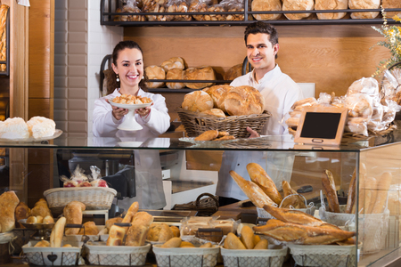 armenian woman: Cheerful man and woman selling fresh pastry and loaves in bread section