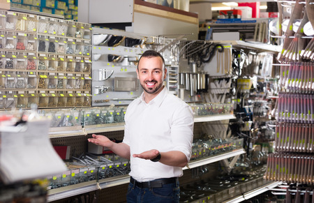 russian man: Young cheerful russian man standing next to showcase with various plastic rawlplugs and  choosing one Stock Photo
