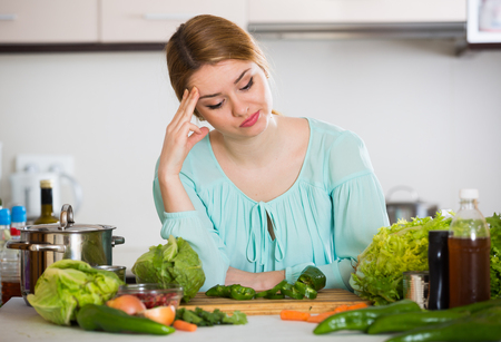 genetically engineered: Female tired of vegetarian meal standing at kitchen table