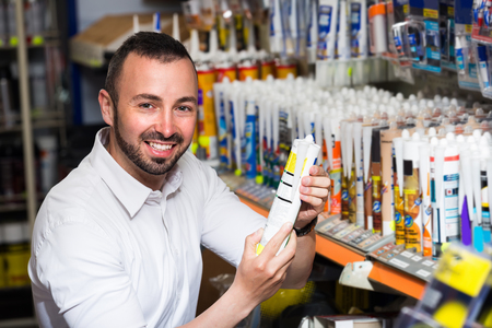 sealant: Portrait of smiling young man selecting sealant bottle in household department