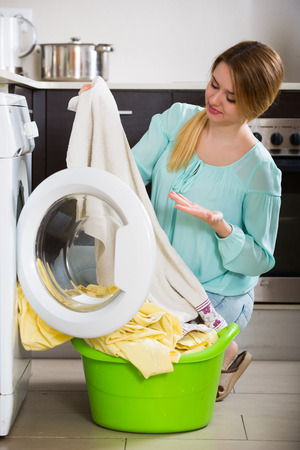 loathsome: Unhappy housewife with dirty bed linen near washing machine