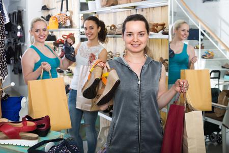 buying shoes: Tres alegre sonriente j�venes clientas compran zapatos de verano en la tienda de moda