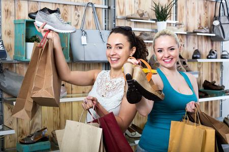 Dos jóvenes mujer alegre juntos de compras en la tienda de moda