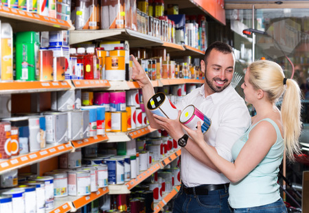 russian man: positive russian man and woman picking paint tin together in household shop