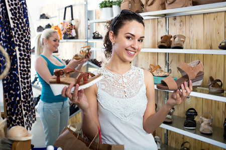 desires 25: Positive young girl choosing a pair of shoes while other customer still  looking Stock Photo