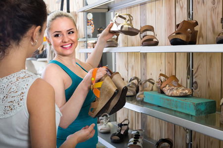 desires 25: Two joyful smiling young women  selecting new shoes in the fashion shoes store Stock Photo