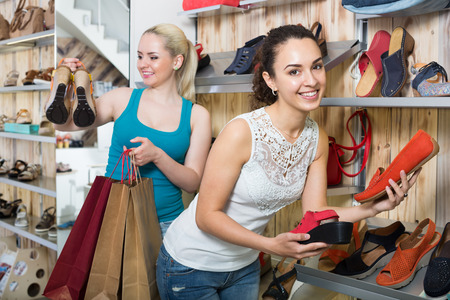 desires 25: Ttwo glad beautiful young women selecting the shoes and chatting among shelves. Focus on right person
