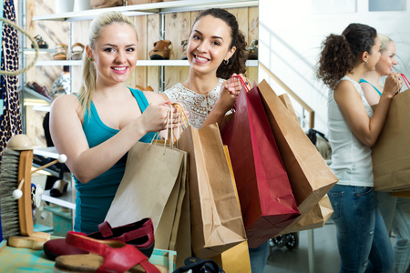 Two adult smiling girls shopping together in the fashion store