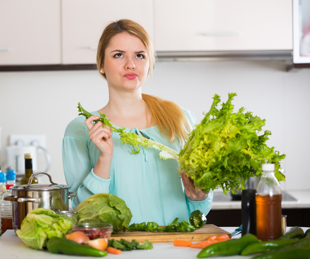 householder: Portrait of upset young woman with rotten vegetables at home