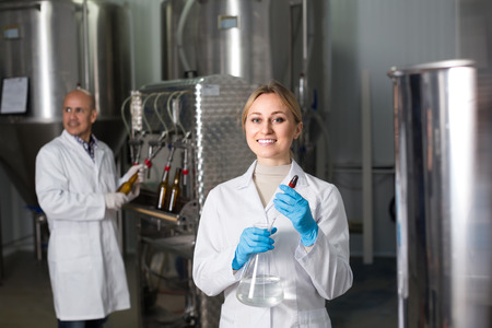 technologist: Portrait of smiling young female technologist and male worker bottling beer at  brewery factory