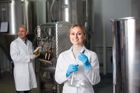 mujer trabajadora: Retrato de la sonrisa técnico joven y embotellado de cerveza trabajador de sexo masculino en la fábrica cervecera