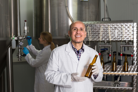 bottling: Cheerful man in white uniform using bottling equipment on brewery