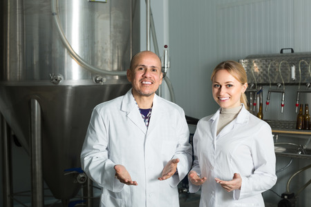 production facility: Happy man and woman working on modern beer production facility Stock Photo