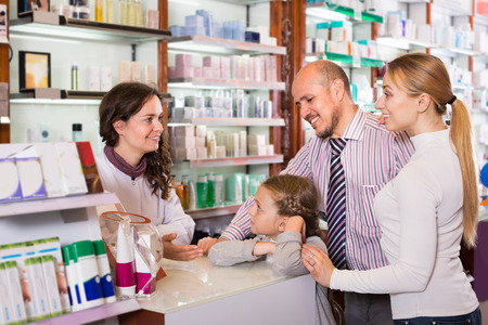 three persons: Cheerful smiling family of three persons getting help of pharmacist at the pharmacy